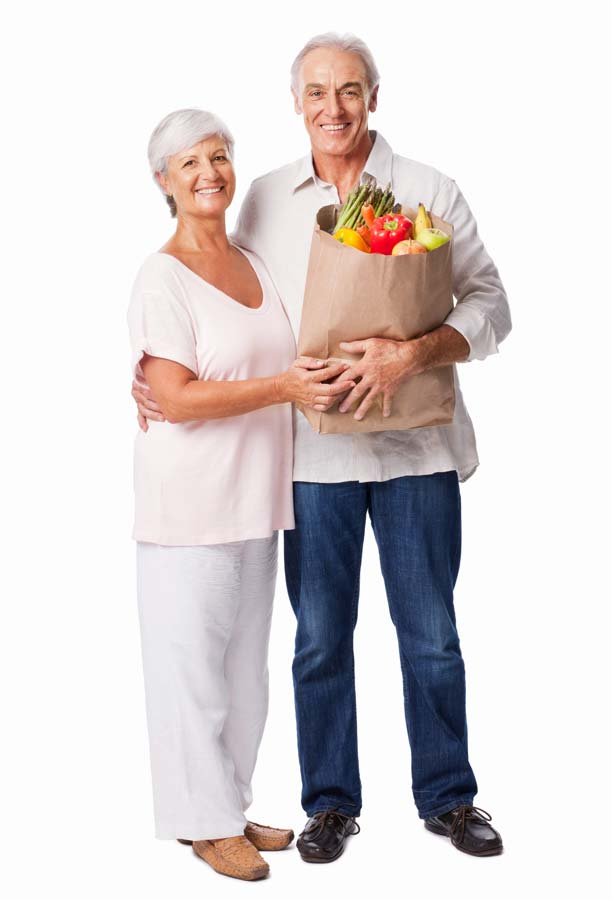 Smiling older couple holding a grocery bag full of produce